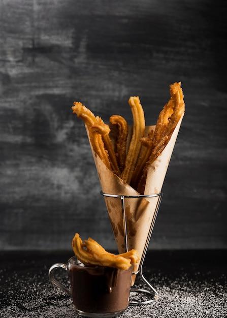 Vista frontal de churros en papel de envolver y chocolate Foto gratis