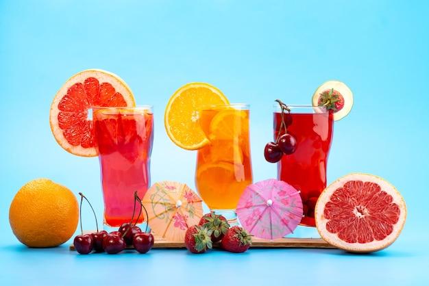 Vista frontal de un cóctel de frutas frescas con frutas rojas frescas y cítricos, enfriamiento con hielo en azul, cóctel de jugo de bebida color de fruta Foto gratis