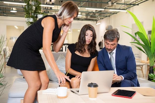 Vista frontal de compañeros de trabajo que trabajan en la computadora portátil Foto gratis
