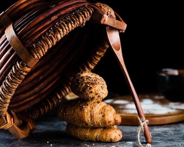 Vista frontal de croissants y cesta Foto gratis