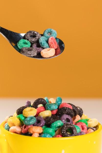 Vista frontal cuchara y tazón con cereales Foto gratis