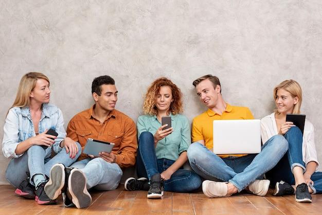 Vista frontal demonios sentado y revisando el teléfono Foto gratis