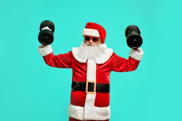 Vista frontal del deportivo santa claus sosteniendo dumbbels. retrato aislado del hombre mayor divertido en traje de navidad y gafas de sol posando Foto gratis