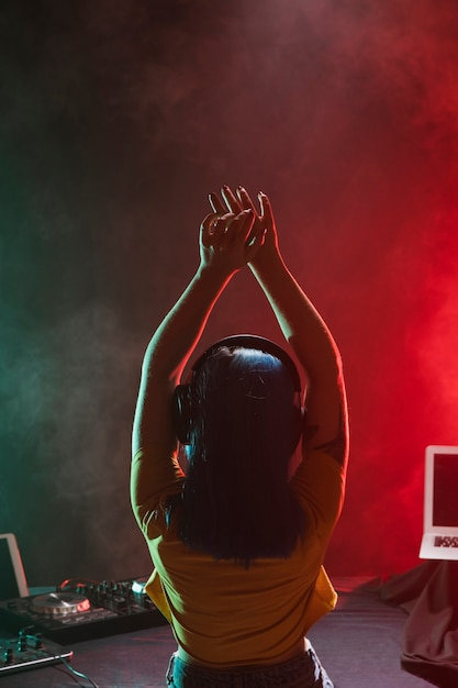 Vista frontal dj femenino con las manos levantadas por encima de la cabeza Foto gratis