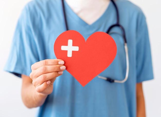 Vista frontal de la doctora con corazón de papel Foto Premium