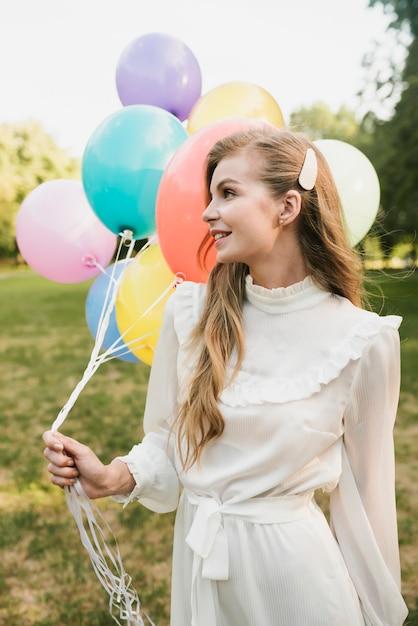 Vista frontal elegante joven con globos Foto gratis