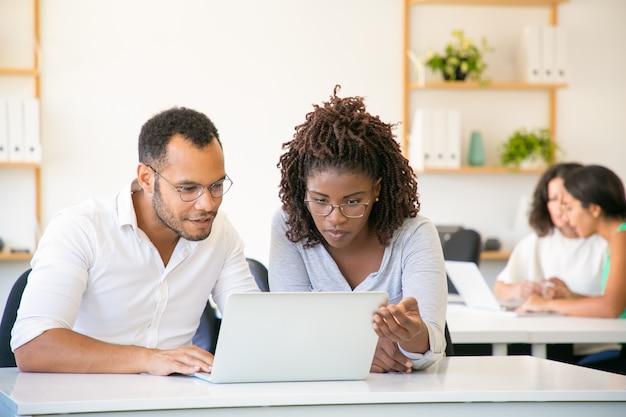 Vista frontal de empleados concentrados que trabajan con laptop Foto gratis