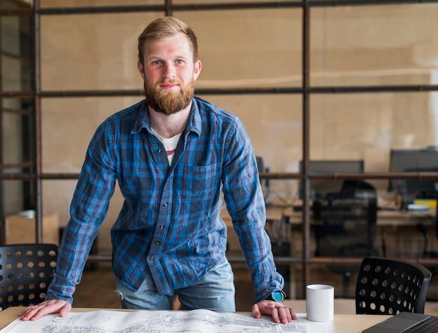 Vista frontal del empresario sonriente de pie frente al escritorio Foto gratis