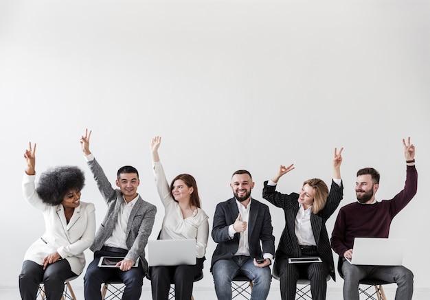 Vista frontal de empresarios con las manos arriba Foto Premium