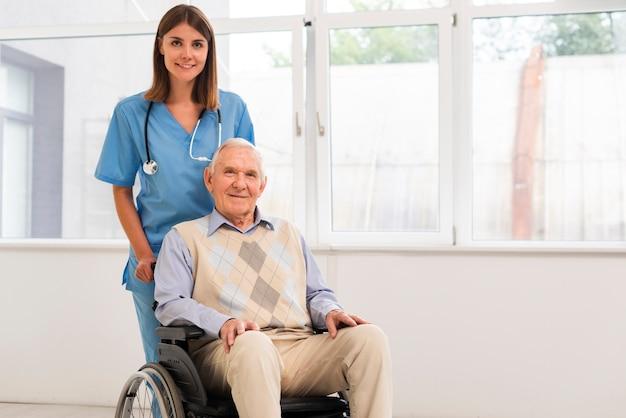 Vista frontal enfermera y anciano mirando a la cámara Foto gratis