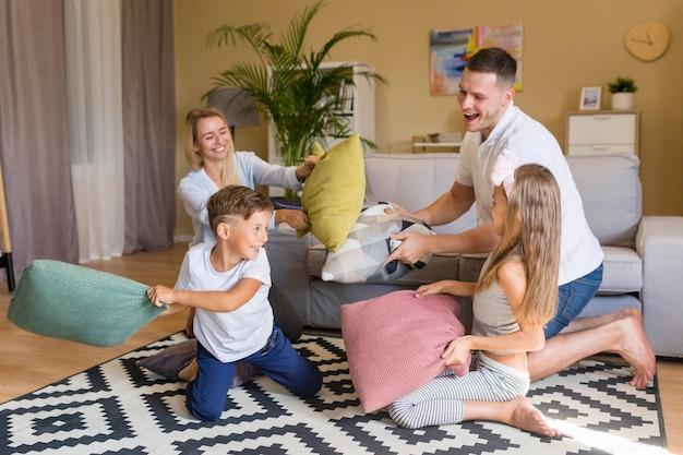 Vista frontal familia feliz jugando con almohadas Foto gratis