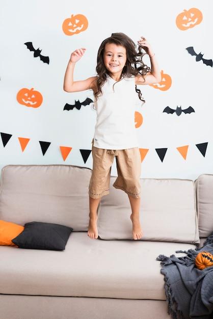 Vista frontal feliz niña saltando en el sofá Foto gratis