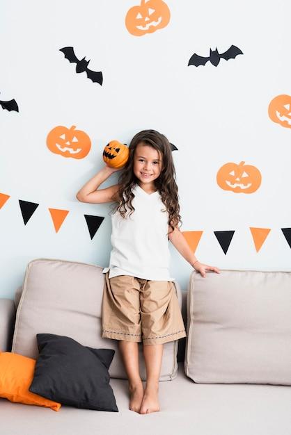 Vista frontal feliz niña sosteniendo una calabaza Foto gratis