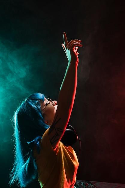 Vista frontal femenina dj viviendo a través de la música reproducida Foto gratis