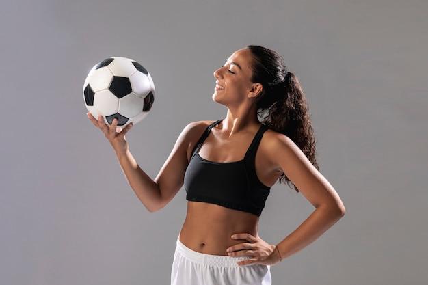 Vista frontal fit mujer sosteniendo bola Foto gratis
