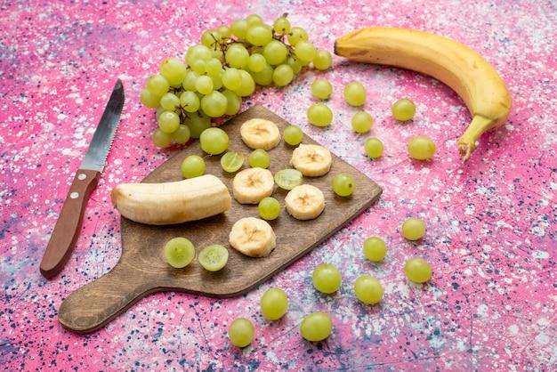 Vista frontal de frutas frescas en rodajas, uvas y plátanos en el escritorio púrpura color de jugo suave de frutas Foto gratis