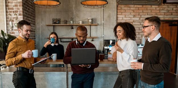 Vista frontal de la gente reunida con una taza de café Foto gratis