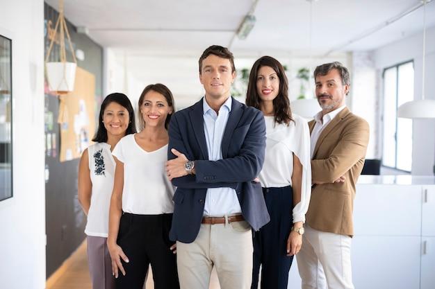 Vista frontal del grupo de compañeros de trabajo posando Foto gratis