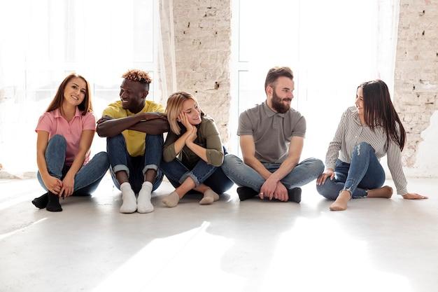Vista frontal grupo de jóvenes amigos en el piso Foto gratis
