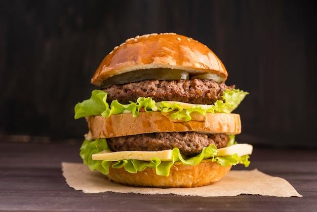 Vista frontal hamburguesa frente a pared de madera Foto gratis