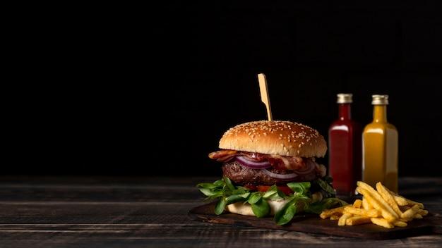 Vista frontal de hamburguesas y papas fritas en la mesa con salsas y espacio de copia Foto gratis