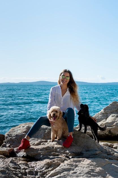 Vista frontal hembra con caniche en el mar Foto gratis