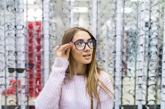 Vista frontal de la hermosa chica en suéter blanco pruebe gafas en tienda profesional en Foto gratis