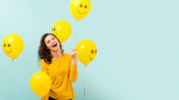 Vista frontal de hermosa mujer con globos Foto gratis