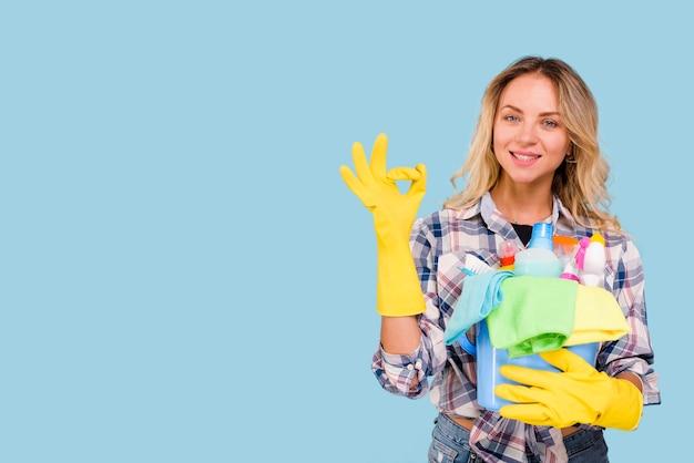 Vista frontal de la hermosa mujer mostrando signo bien mientras sostiene productos de limpieza en balde contra el fondo azul Foto gratis