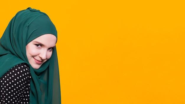 Vista frontal de la hermosa mujer sonriendo delante de fondo amarillo Foto gratis