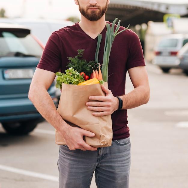 Vista frontal hombre con bolsa de supermercado | Foto Gratis