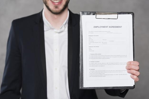 Vista frontal del hombre con contrato para un nuevo trabajo Foto gratis
