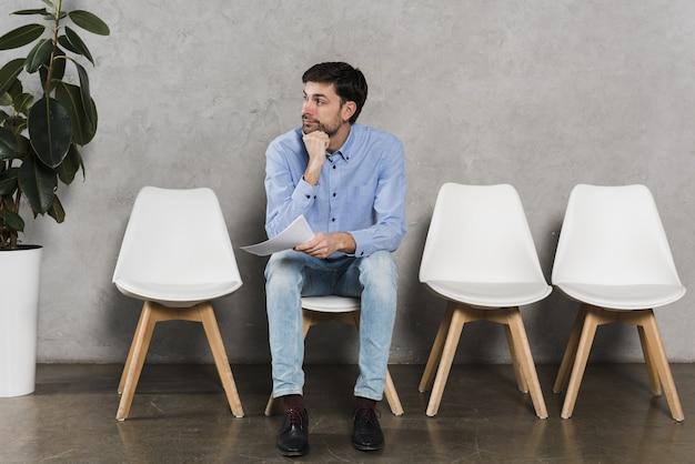 Vista frontal del hombre con currículum y esperando su entrevista de trabajo Foto Premium