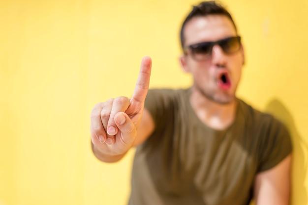 Vista frontal de un hombre fresco desenfoque diciendo que no con gafas de sol contra una pared amarilla Foto Premium