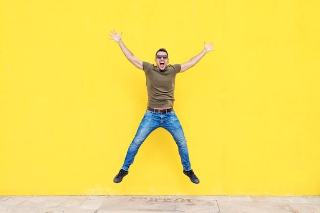 Vista frontal de un hombre joven con gafas de sol saltando contra una pared amarilla brillante en un día soleado Foto Premium