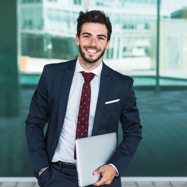 Vista frontal hombre con laptop mirando a cámara Foto gratis