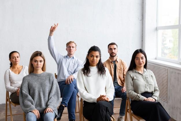Vista frontal del hombre levantando la mano para preguntar en una sesión de terapia de grupo Foto gratis