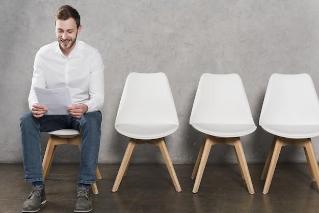 Vista frontal del hombre leyendo su currículum antes de tener su entrevista de trabajo Foto Premium