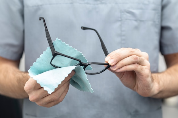 Vista frontal del hombre limpiando sus gafas Foto Premium