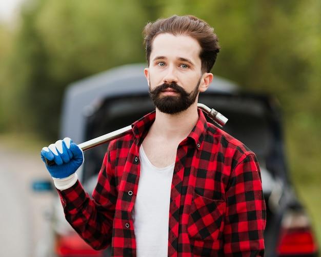 Vista frontal del hombre con llave de neumático Foto gratis