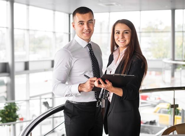 Vista frontal hombre y mujer en concesionario Foto Premium