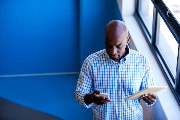 Vista frontal del hombre de negocios de pie mientras usa la tableta digital Foto Premium