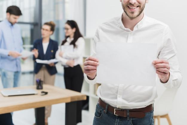 Vista frontal del hombre en la oficina con papel en blanco Foto Premium