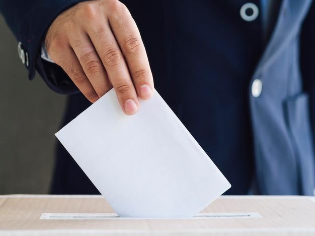 Vista frontal hombre poniendo una boleta vacía en la casilla electoral Foto Premium