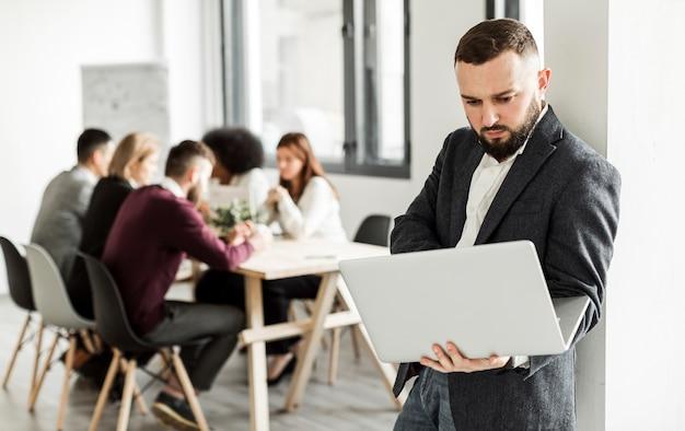 Vista frontal del hombre que sostiene una computadora portátil Foto gratis