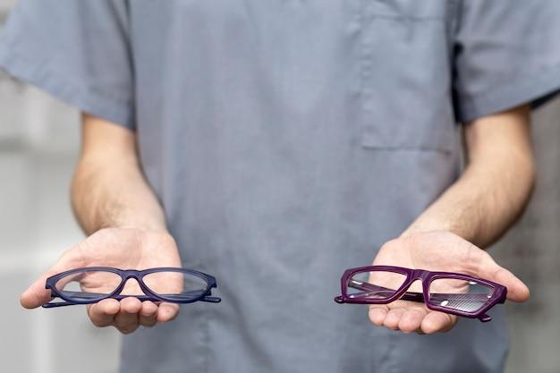 Vista frontal del hombre que sostiene un par de anteojos en cada mano Foto gratis