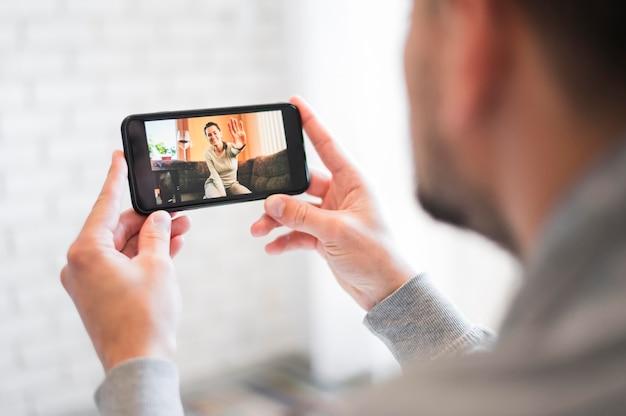 Vista frontal del hombre que tiene una videollamada Foto gratis