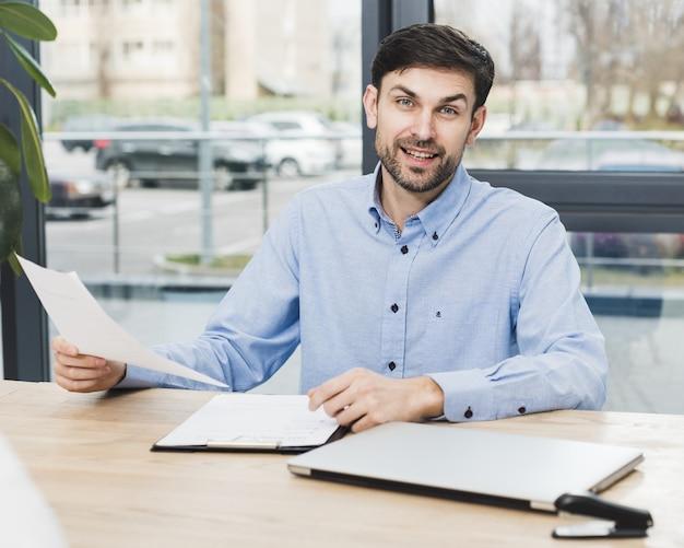 Vista frontal del hombre de recursos humanos en el escritorio con una entrevista Foto Premium