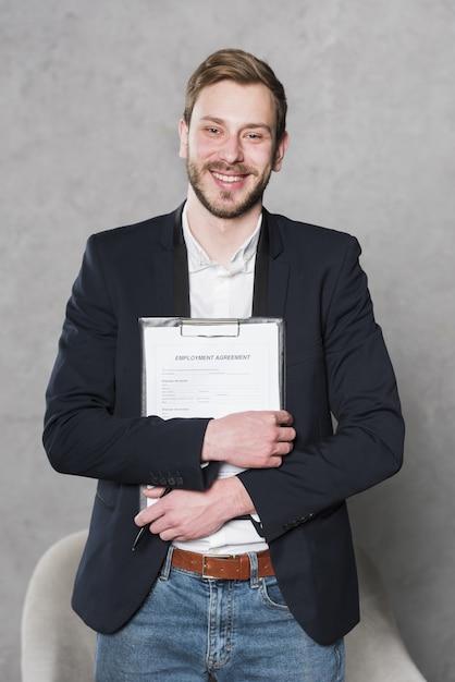 Vista frontal del hombre sonriente con contrato para nuevo trabajo Foto Premium