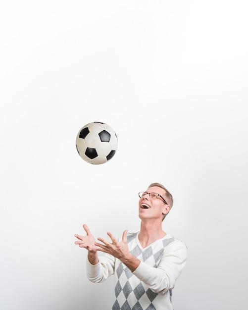 Vista frontal del hombre sonriente jugando con una pelota de fútbol Foto gratis
